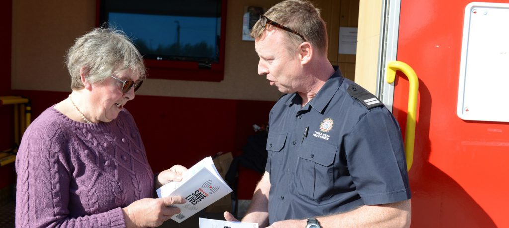 A firefighter talks a woman through a smoke alarm leaflet