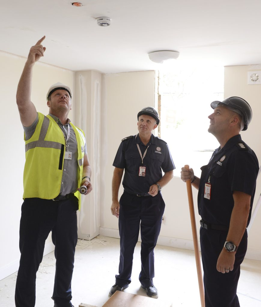 A business manager and TWFRS business safety team inspect a smoke alarm
