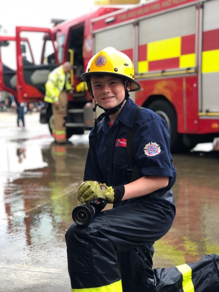 A fire cadet aims a hose